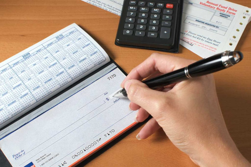 Woman's hand writing a check to pay the bills, with calculator and an invoice on the desktop