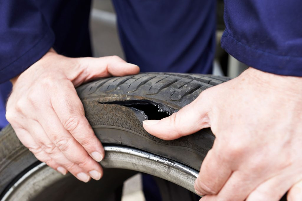 A man's hands showing a torn out tire due to blow out