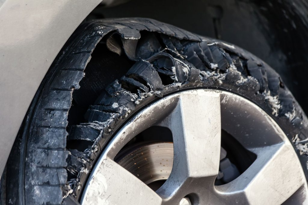 An up close view of a destroyed blown out car tire