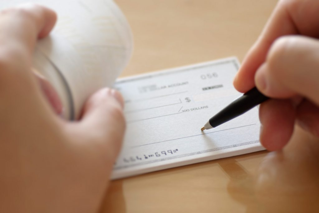 A right handed person about to write a check
