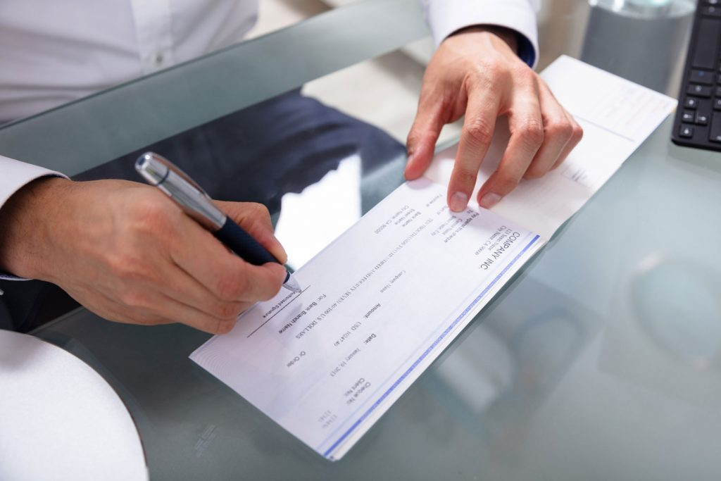 Businessman's Hand Signing Check On Glass Desk