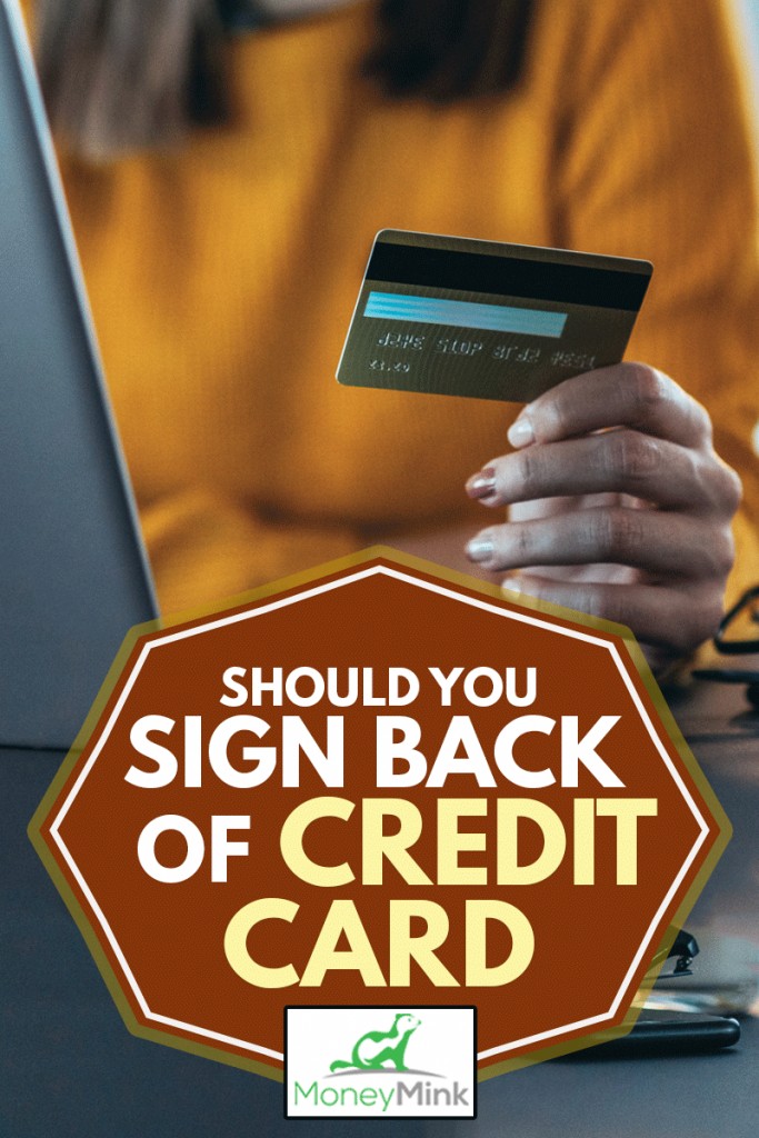 A woman's hand showing the back of her credit card, Should You Sign Back Of Credit Card