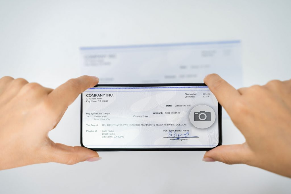 Woman Taking Photo of a Check To Make Remote Bank Deposit